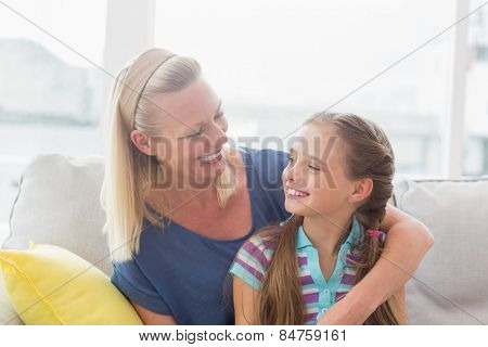 Happy mother and daughter looking at each other while sitting on sofa at home