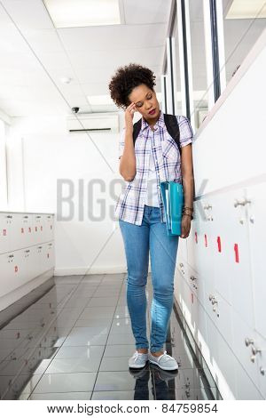 Full length of tensed young woman with folders standing in office