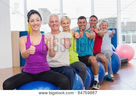 Portrait of smiling people sitting on exercising balls gesturing thumbs up in gym