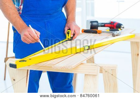 Midsection of carpenter working at workbench in bright office