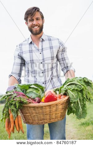 Handsome farmer with basket of veg on a sunny day