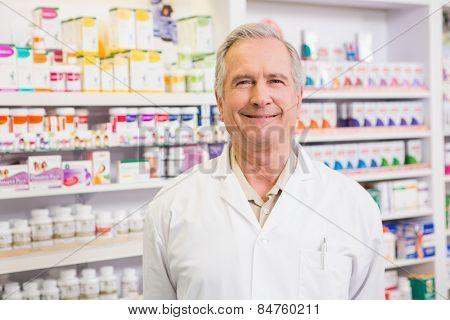 Smiling senior pharmacist standing in the pharmacy