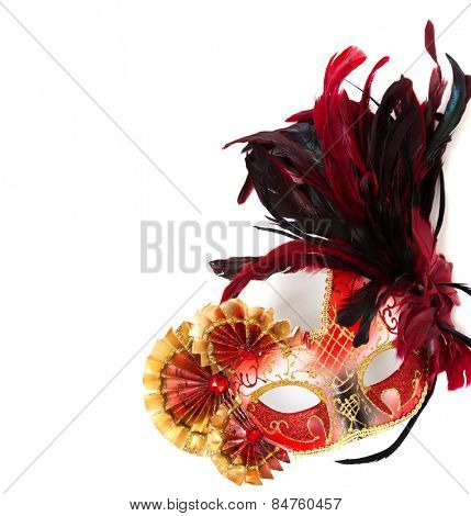 A red, elaborate mardi gras or venetian mask with feathers on a white background