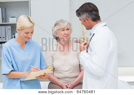 Male doctor consoling patient while nurse writing reports in clinic