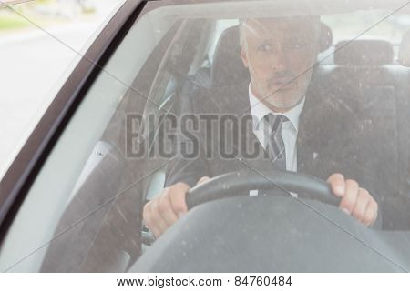 Perplexed man sitting at the wheel in his car