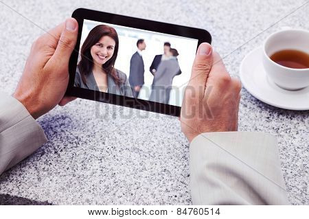 Businessman holding small tablet at table against happy businesswoman posing while her team discussing