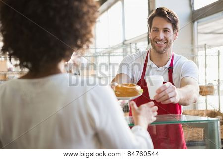 Smiling waiter giving lunch and hot drink to customer at the bakery