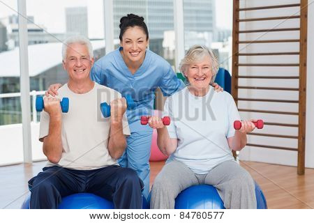 Portrait of happy female instructor with arms around senior couple in gym