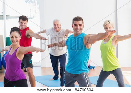 Happy men and women doing warrior pose in yoga class