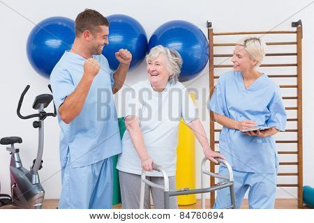 Smiling therapists with invalid woman in fitness studio