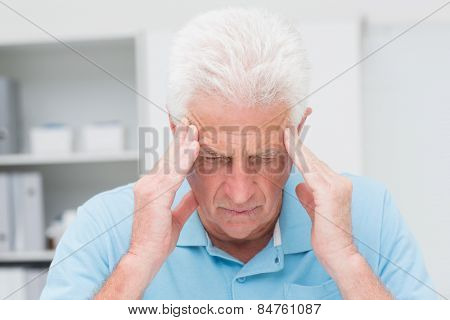 Senior male patient suffering from headache in clinic