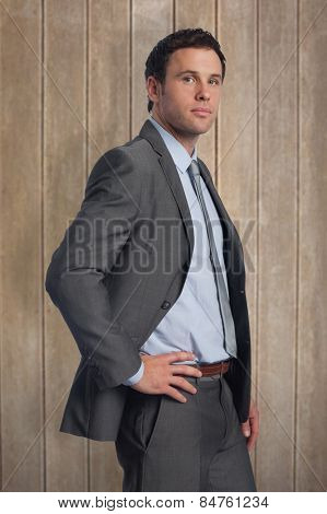 Serious businessman with hand on hip against wooden surface with planks