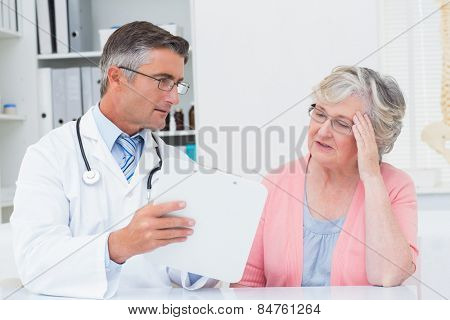 Male doctor explaining prescriptions to tensed senior woman in clinic
