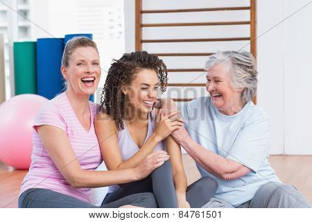 Playful female friends sitting together in gym