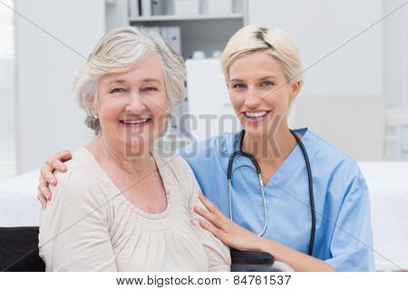 Portrait of friendly nurse with arm around senior patient in clinic