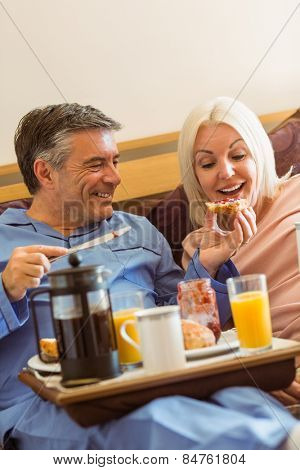 Happy mature couple having breakfast in bed at home in bedroom