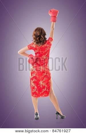 Chinese woman dress traditional cheongsam and boxing gloves, rear view full length portrait isolated.