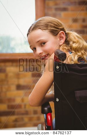Portrait of cute little girl sitting in wheelchair in school