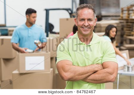 Portrait of a smiling volunteer with arms crossed in a large warehouse