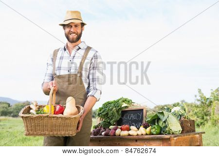 Farmer holding basket of vegetables at market on a sunny day