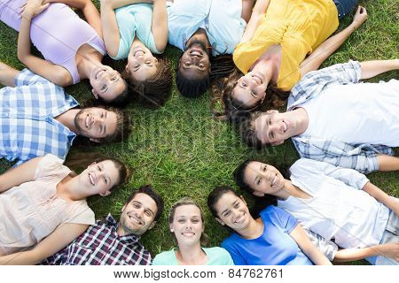 Happy friends in the park lying in circle on a sunny day