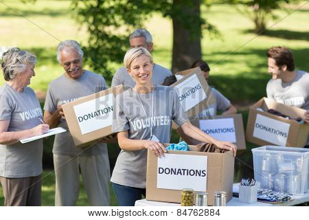 Happy family holding donations boxes on a sunny day
