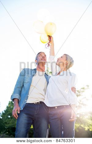 Cute couple holding up balloons at the park on a sunny day