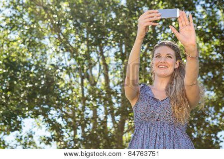 Pretty blonde taking a selfie on a summers day
