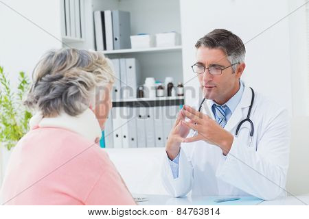 Male doctor discussing with female patient wearing neck brace in clinic