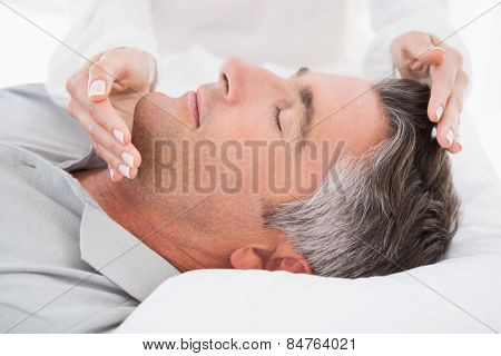 Therapist working with man in medical office