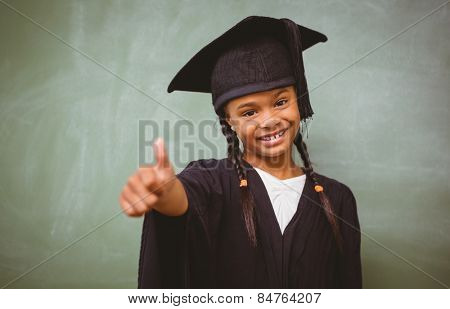 Portrait of cute little girl in graduation robe gesturing thumbs up