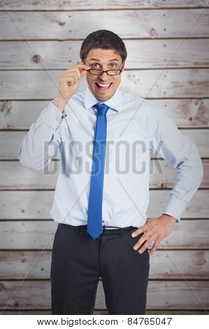Thinking businessman tilting glasses against wooden planks