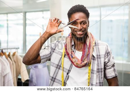 Portrait of happy male fashion designer holding scissors