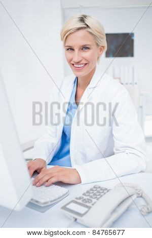 Portrait of confident female doctor using computer in clinic