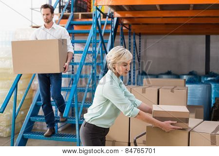 Warehouse managers loading a trolley in a large warehouse