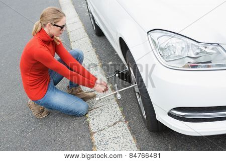 Young woman replacing tire of her car