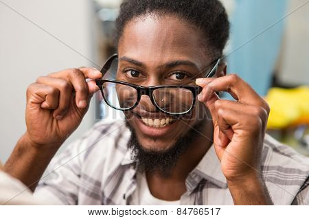 Close up portrait of happy male fashion designer holding eye glasses