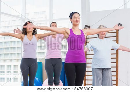 Female friends with arms outstretched exercising in gym