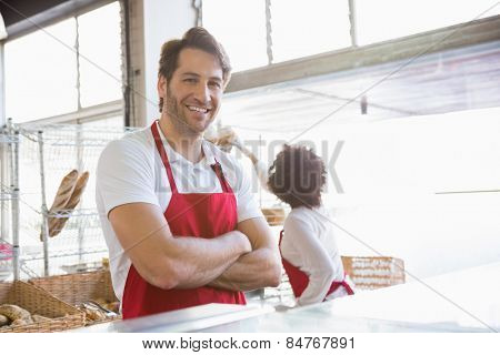 Portrait of a happy waiter with arms crossed at the bakery