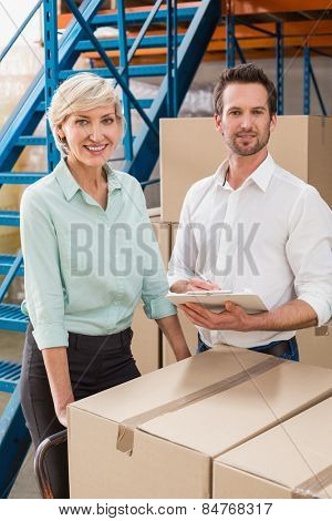 Smiling warehouse managers with clipboard in a large warehouse