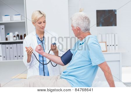 Female doctor checking senior mans blood pressure in clinic