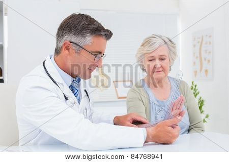 Male physiotherapist examining female patients wrist with goniometer in clinic