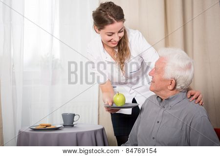 Helpful Nurse And Smiling Pensioner