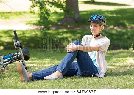 Injured blonde touching her painful knee on a sunny day