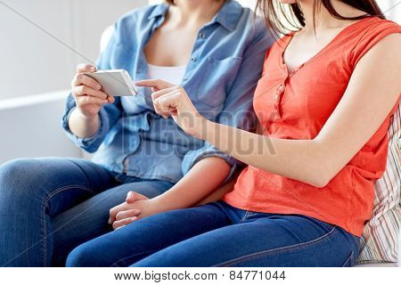 people, homosexuality, same-sex marriage, gay and love concept - close up of happy lesbian couple with smartphone at home