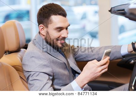 auto business, car sale, consumerism, technology and people concept - happy man sitting in car with smartphone at auto show or salon