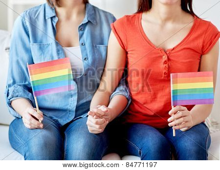 people, homosexuality, same-sex, gay pride and love concept - close up of happy lesbian couple holding rainbow flags at home