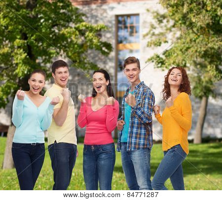 friendship, education, summer vacation, teamwork and people concept - group of smiling teenagers showing triumph gesture over campus background