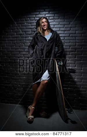 Pretty woman with skateboard against  brick background