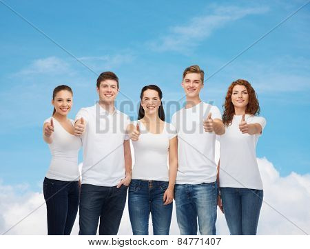 advertising, dream, future and people concept - group of smiling teenagers in white blank t-shirts showing thumbs up over blue sky with white cloud background